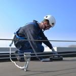 man aangelijnd aan valbeveiliging onderhoud aan dak
