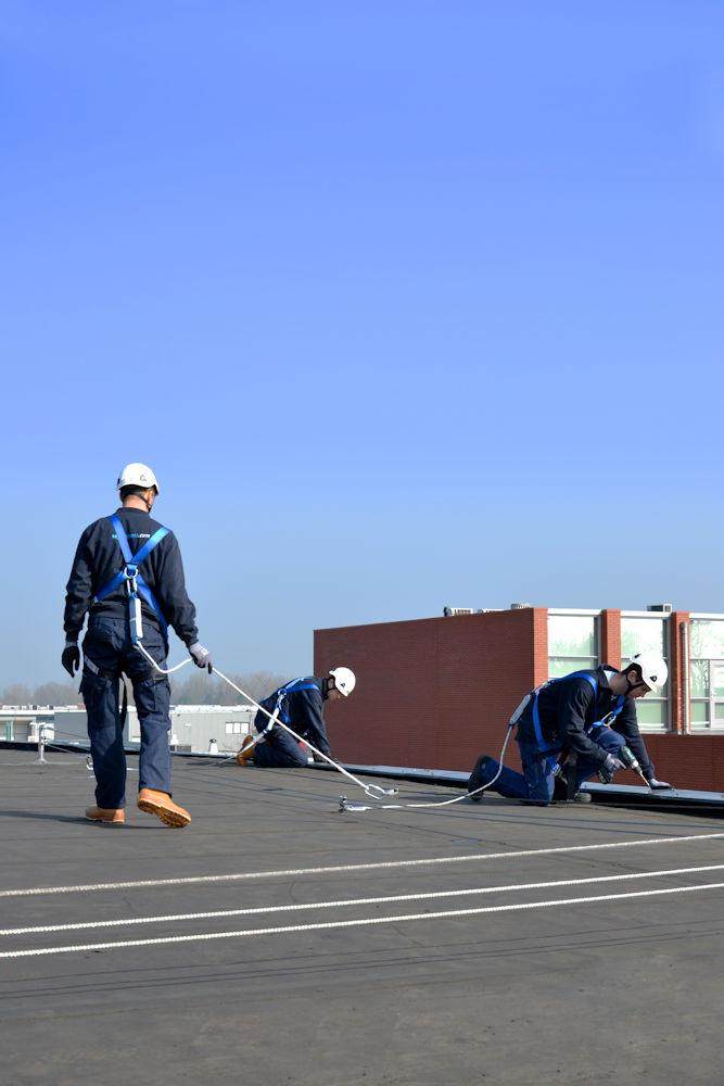 manenn aan het werk op dak aangelijnd aan valbeveiliging