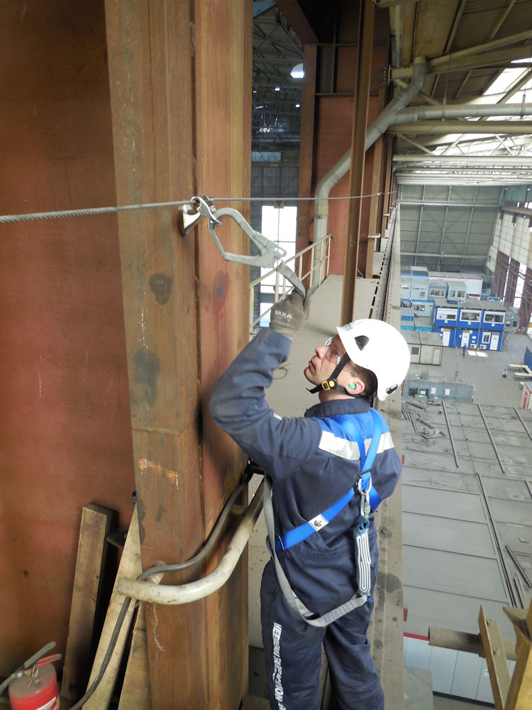 man aangelijnd aan valbeveiliging fabriekshal
