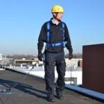 man aangelijnd aan valbeveiliging op dak