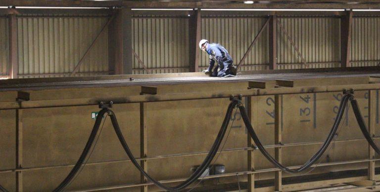 man aangelijnd met valbeveiliging in fabriekshal