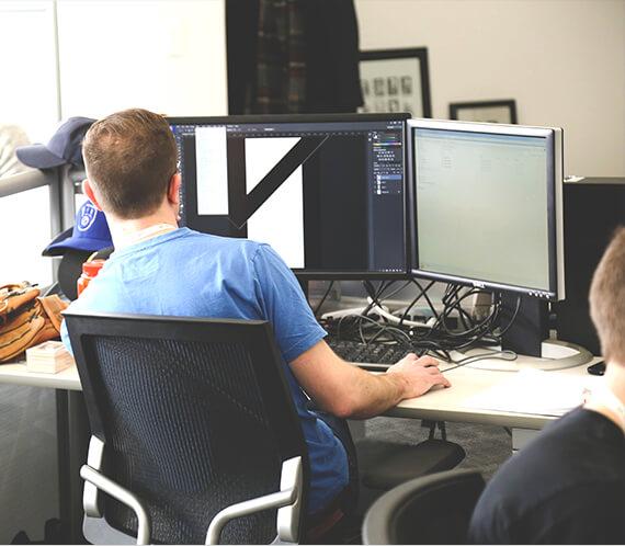 man achter bureau met beeldschermen maakt een advies tekening