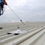 man op dak aangelijnd aan valbeveiliging