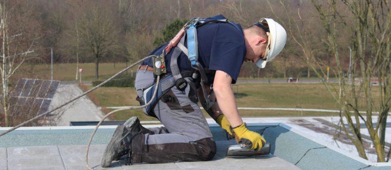 persoon met persoonlijke beschermings middelen op dak harnas