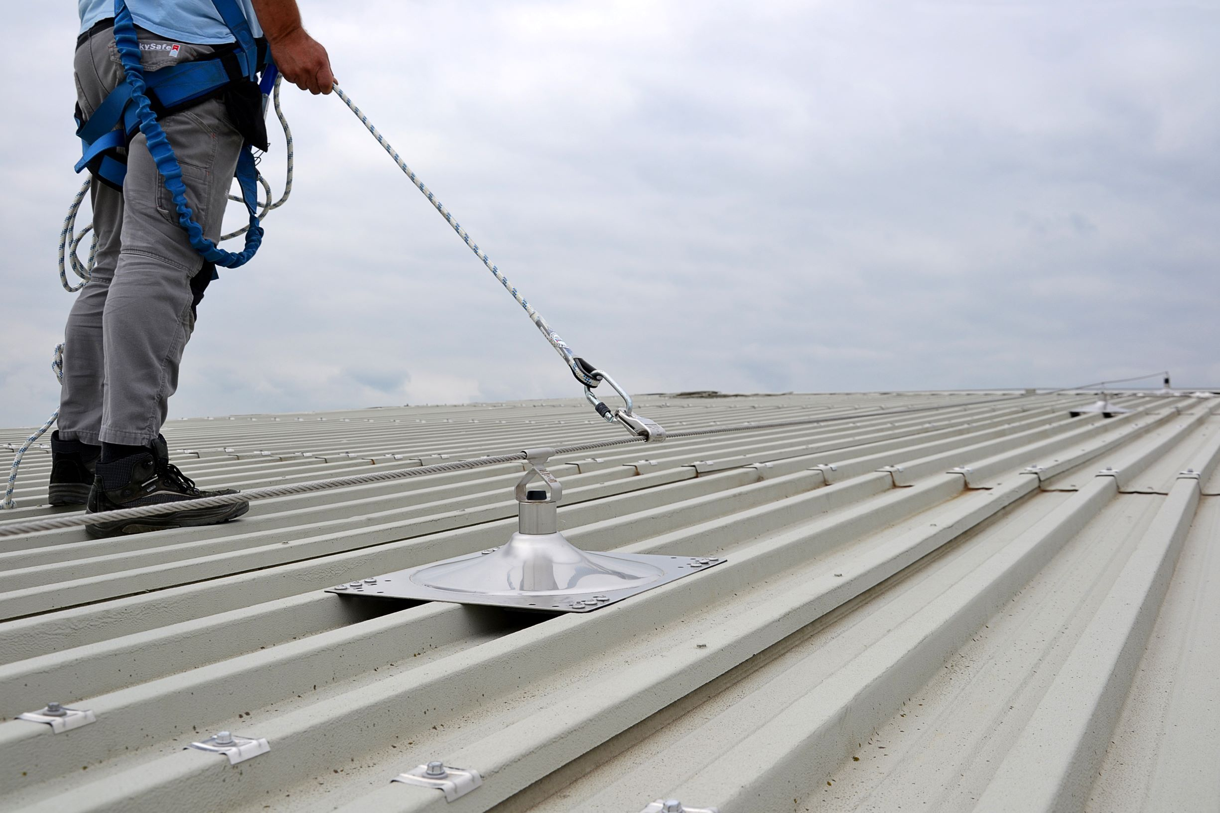 Man aangelijnd aan valbeveiliging kabelsysteem op metalen dak
