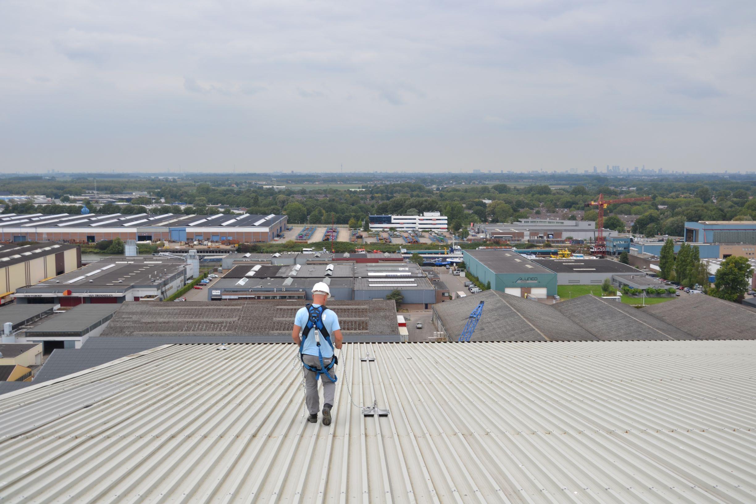Persoon op metaal dak veilig aan valbeveiliging