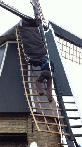 Man in molen met valbeveiliging harnas